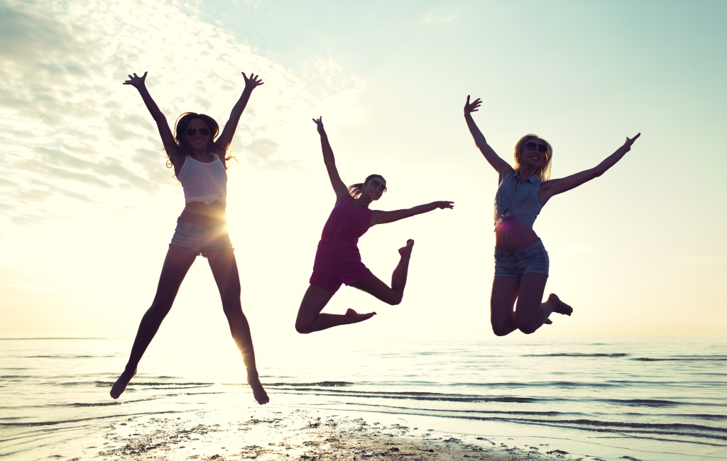 friendship, summer vacation, freedom, happiness and people concept - group of happy female friends dancing and jumping on beach